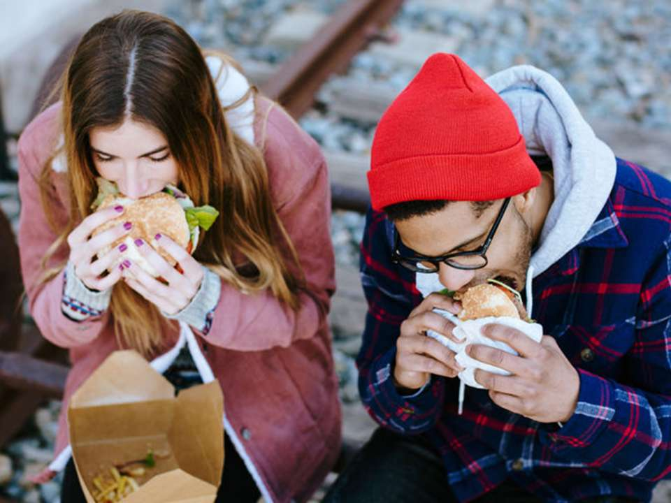 Two people eating burgers.