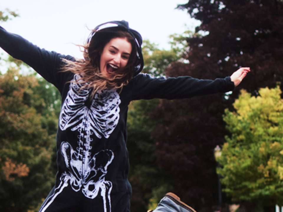 Woman in skeleton costume jumps in the air