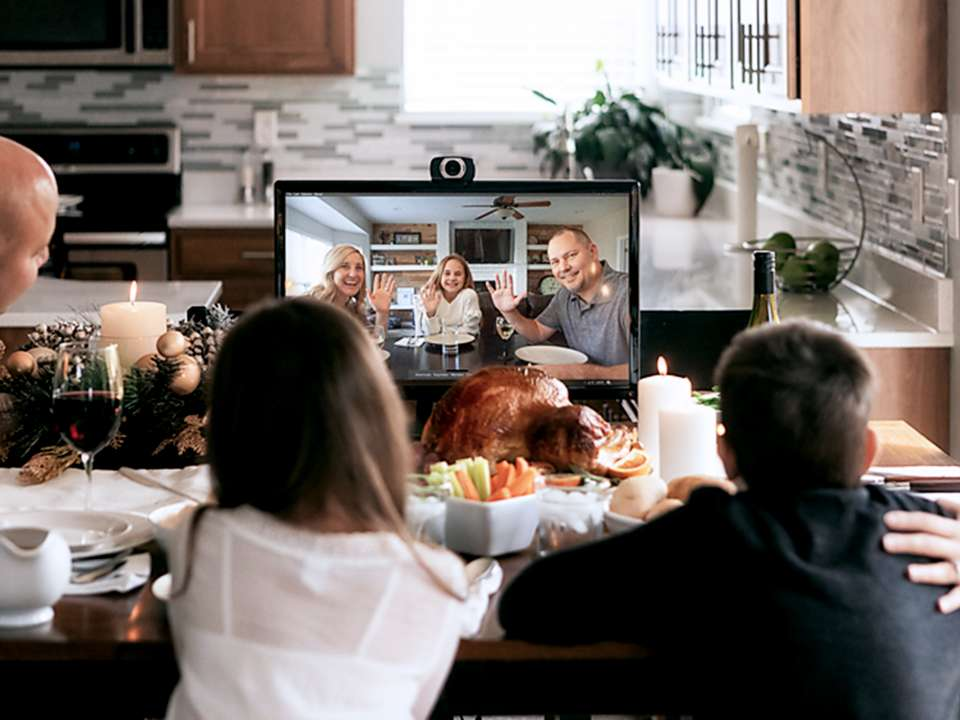Family eating holiday meal and video chatting loved ones.