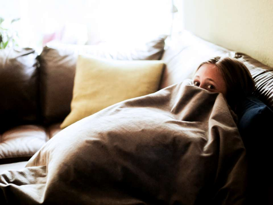 A woman sits on a couch hiding under a blanket.