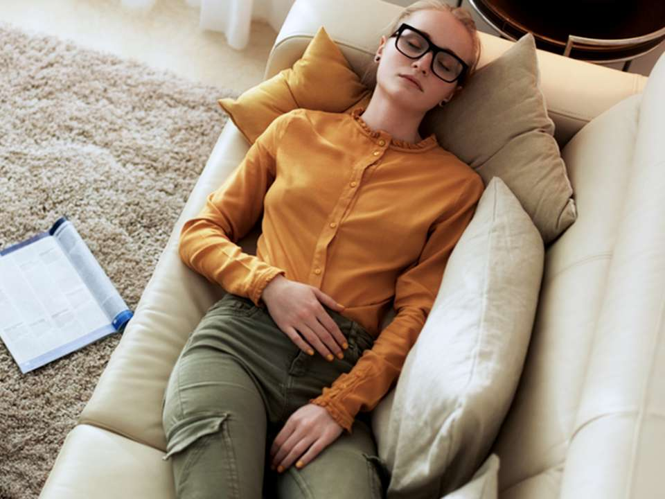 A woman lays on a couch holding her stomach.
