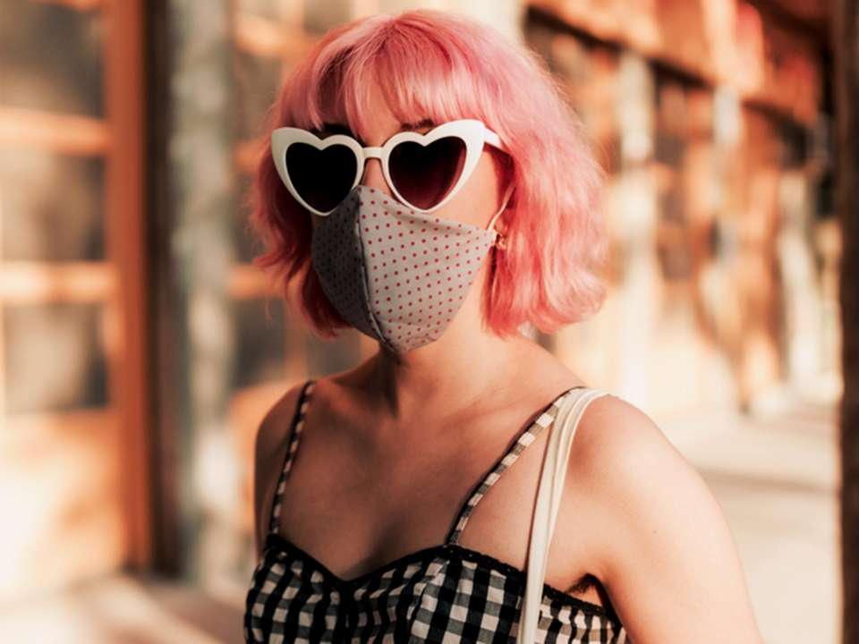 A light-skinned woman with short pink hair wears a face mask and heart-shaped sunglasses.