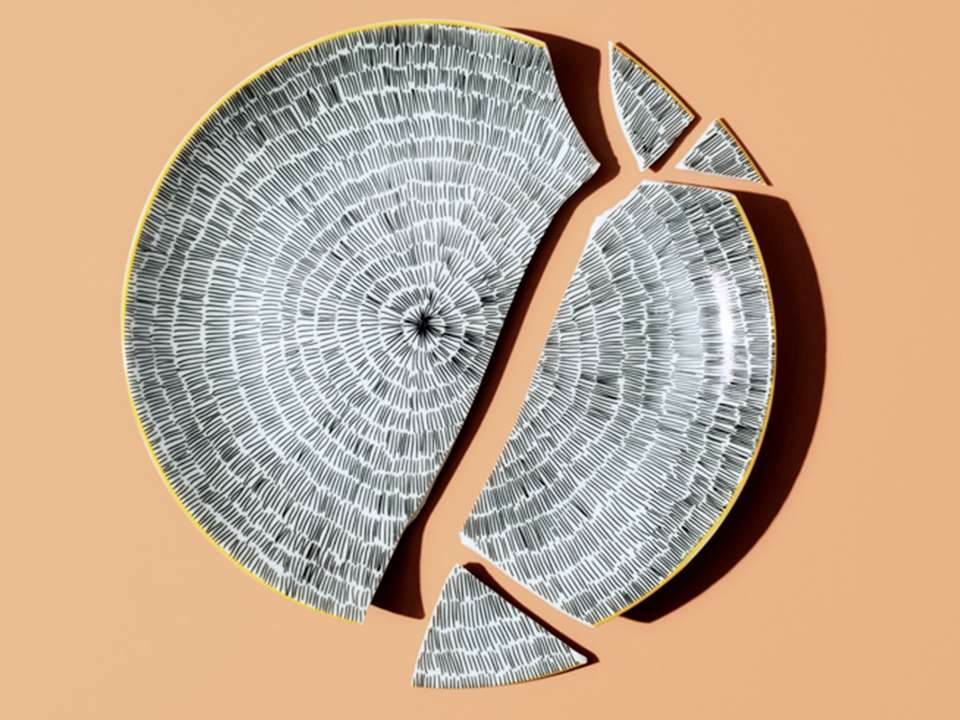 A patterned broken plate on a peach background.
