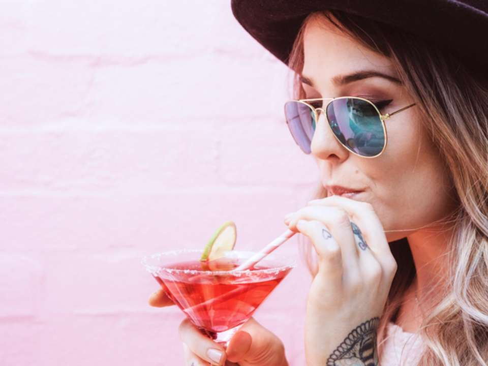 A white woman wearing a hat and sunglasses sips from a cocktail standing in front of a pink-painted brick wall.