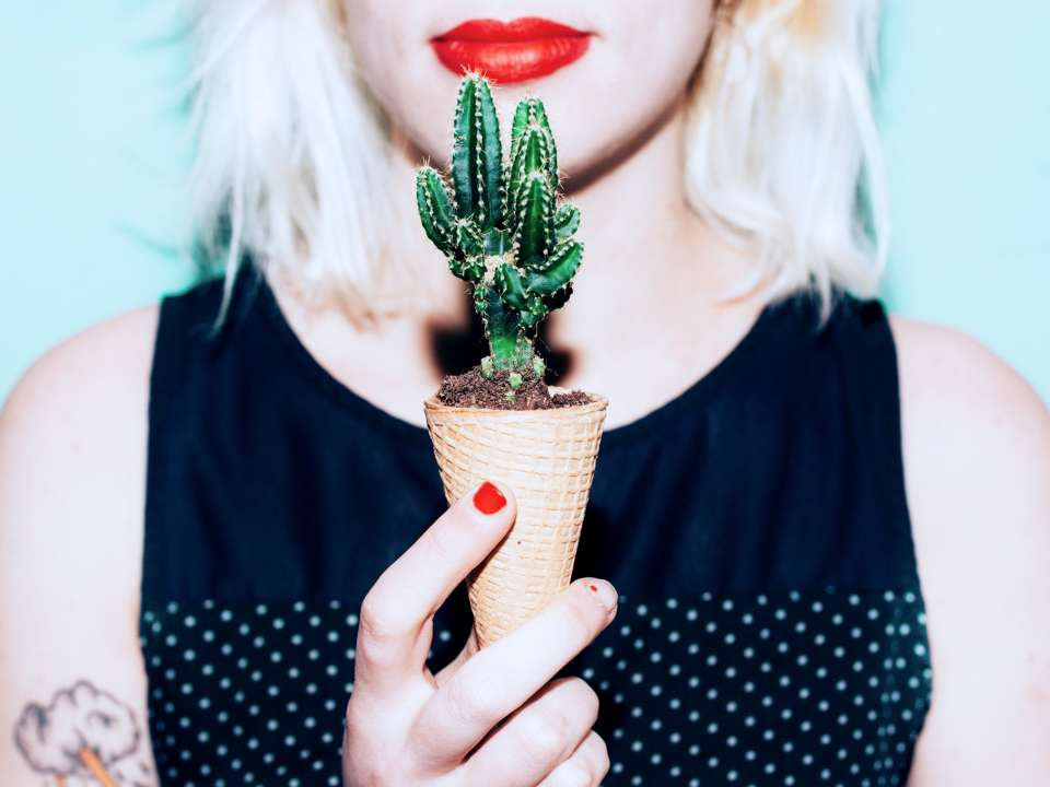 A woman holds a cactus in an ice cream cone.