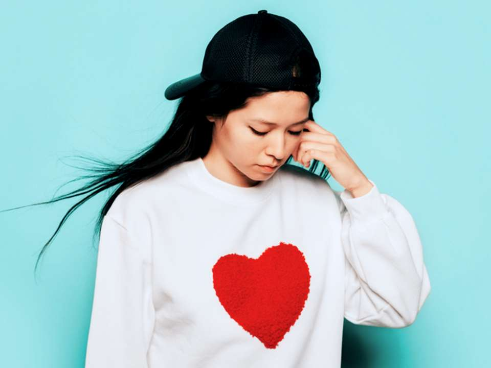 Woman wearing a sweatshirt with a heart on it.