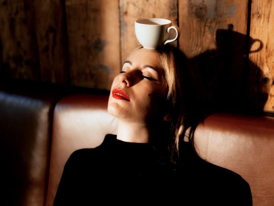 A woman with a coffee cup balanced on her head.
